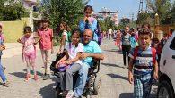 Kızlarını akülü aracıyla okula götürüyor